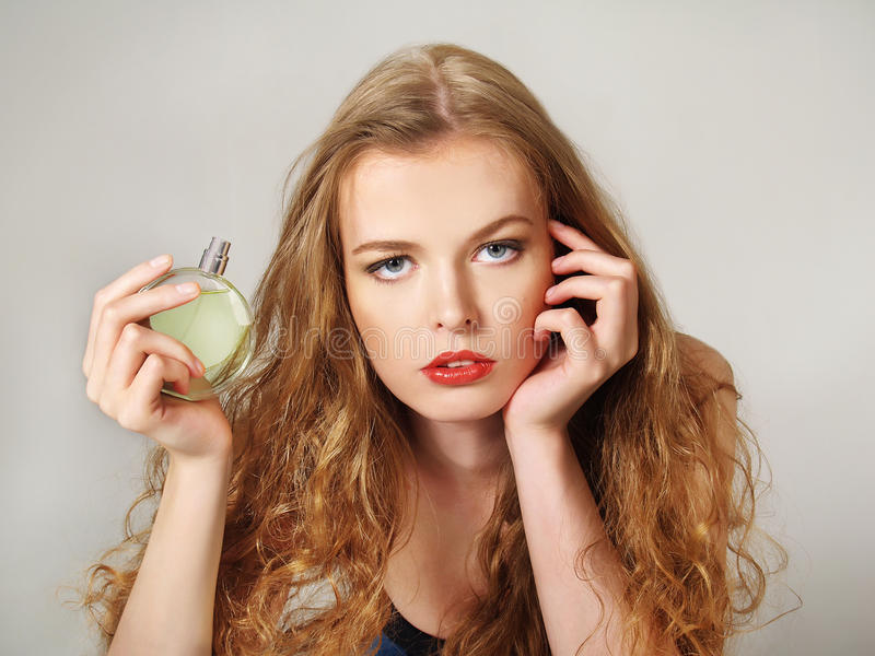 Beautiful girl with bottle of perfume royalty free stock photography