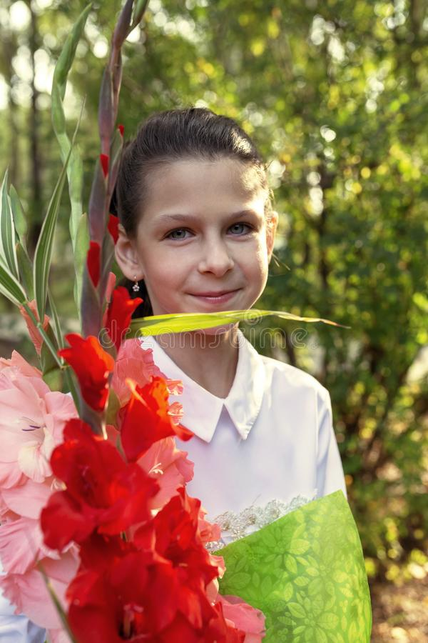 Girl with a bouquet of gladioli on the first day of school royalty free stock photos