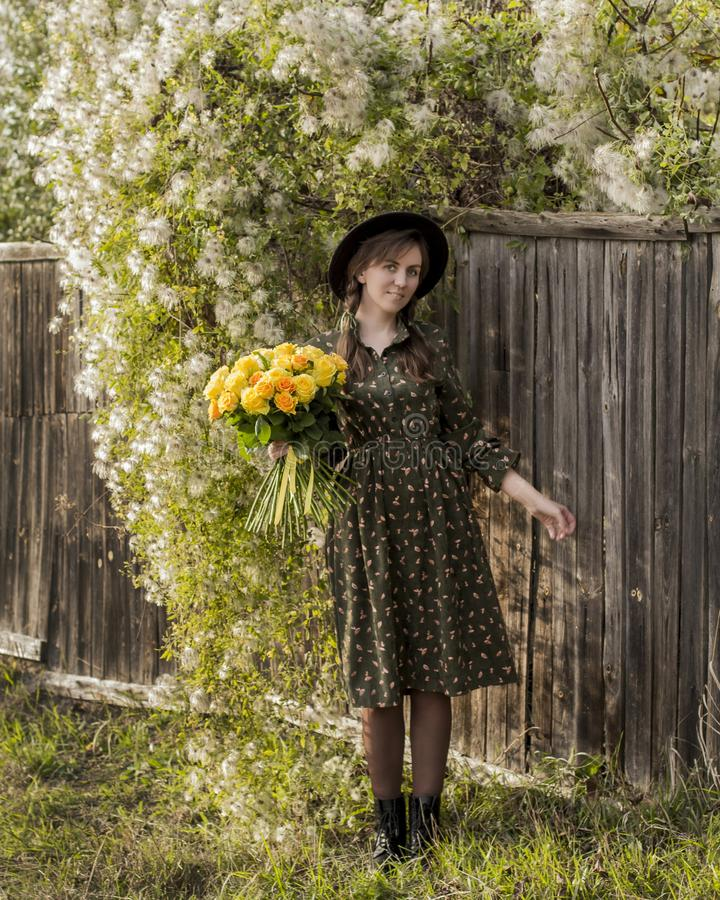 Beautiful girl with a bouquet of yellow roses. Woman with model appearance in a hat. Pretty woman near a vintage fence. Teenager. Girl in a black hat and roses royalty free stock images