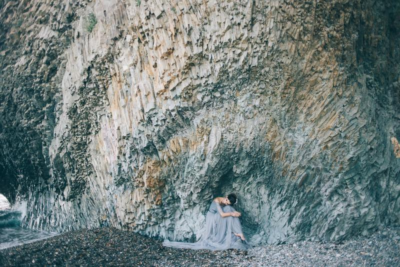 Beautiful girl bride in a long blue dress sitting on the sea near the cliff. With his head bowed, hugging her knees stock photo