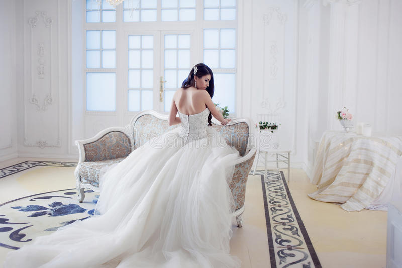 Beautiful girl bride in a magnificent dress sitting on the sofa. Luxurious light interior stock photography