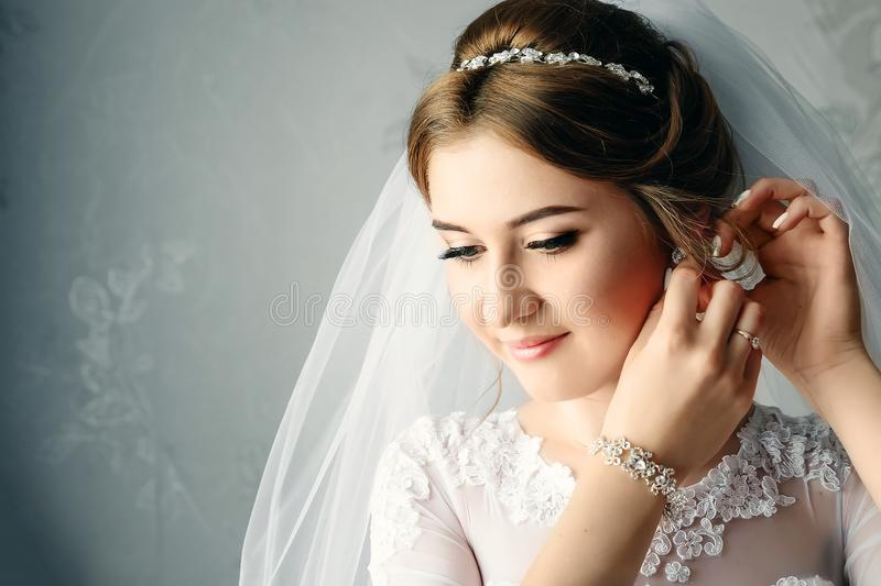 Beautiful girl, bride in a white dress on the background of the apartment. Wedding, bride`s gathering, family creation stock photography