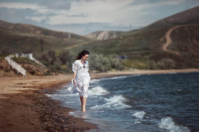 Beautiful girl, bride, in white dress, barefoot, runs on the beach, on the water and laughs. stock photography