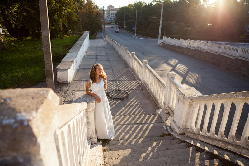 Beautiful girl bride in a white dress in the rays of the sun royalty free stock photography