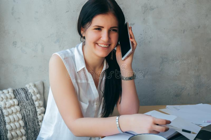 Beautiful girl in bright clothes on a gray background emotionally talking on the phone and smiles . Negotiations at work, stock image