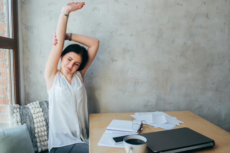 Beautiful girl in bright clothes on a gray background Stretching up with his hands, taking a break .coworking. On the desktop is royalty free stock photography