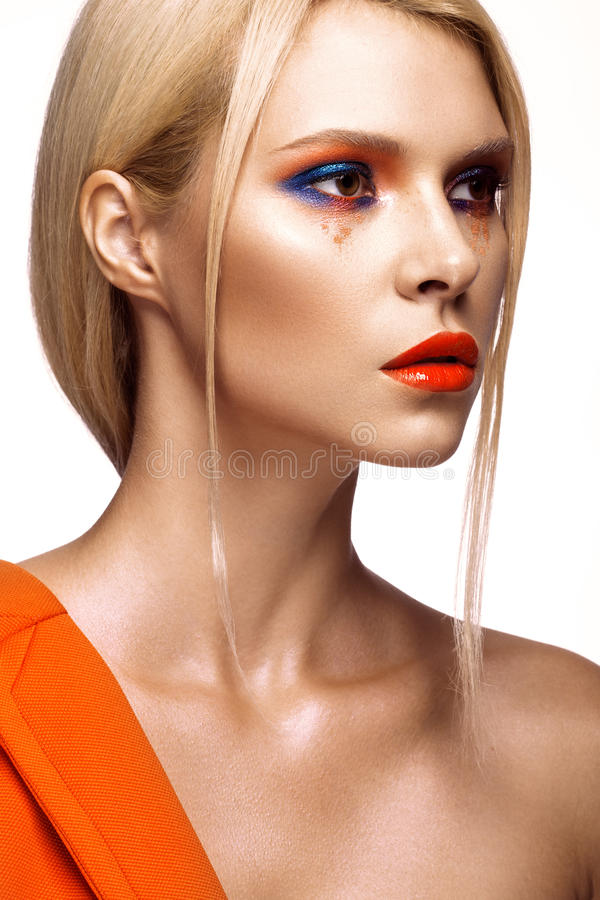 Beautiful girl with bright colored makeup and orange lips. Beauty face. royalty free stock image