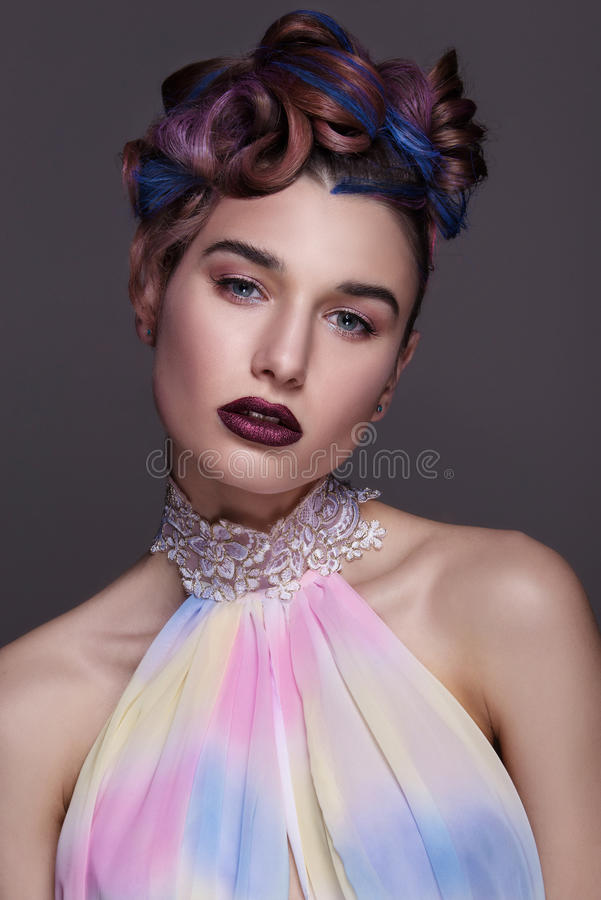 Beautiful girl with bright creative fashion makeup and colorful hairstyle. Studio portrait of beauty face. stock photography