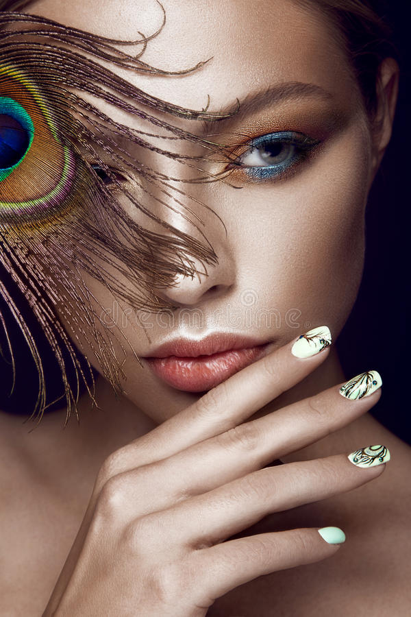 Beautiful girl with bright makeup, manicure design and peacock feather on her face. Art nails. Photos shot in the studio stock photo