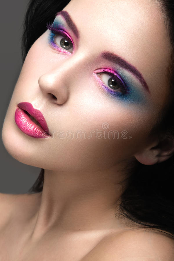 Beautiful girl with bright pink make-up and perfect skin. Beauty face. Festive image. Picture taken in the studio on a gray background royalty free stock image