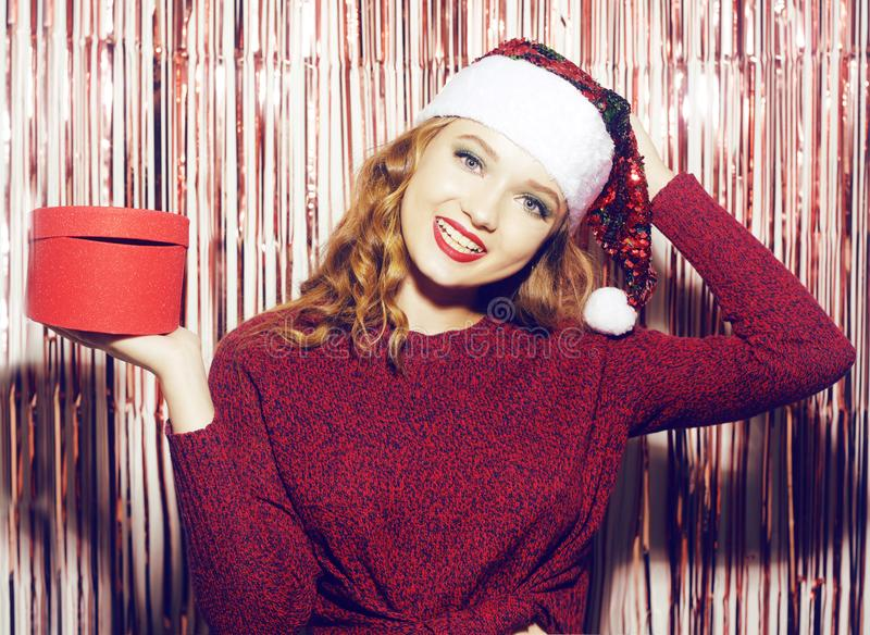 Beautiful girl in a bright santa hat on a shiny background holds a red box with a gift for the new year. Christmas brunette in a stock photos