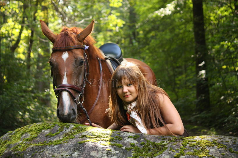 Beautiful girl and brown horse portrait in mysterious forest royalty free stock photo