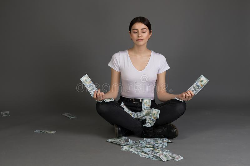 Beautiful girl with brunette hair in white t-shirt meditates with closed eyes while sitting in lotus position. Holding money banknotes in hands stock photo