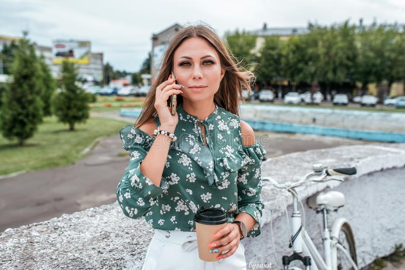 Beautiful girl brunette woman standing in park behind the back of the bike. Phone in hand a mug with hot coffee or tea stock images