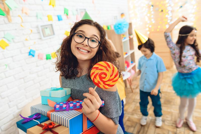 Beautiful girl with bunch of presents is holding colored lollipop in hand at her birthday. Happy birthday party. Children`s fun concept royalty free stock image