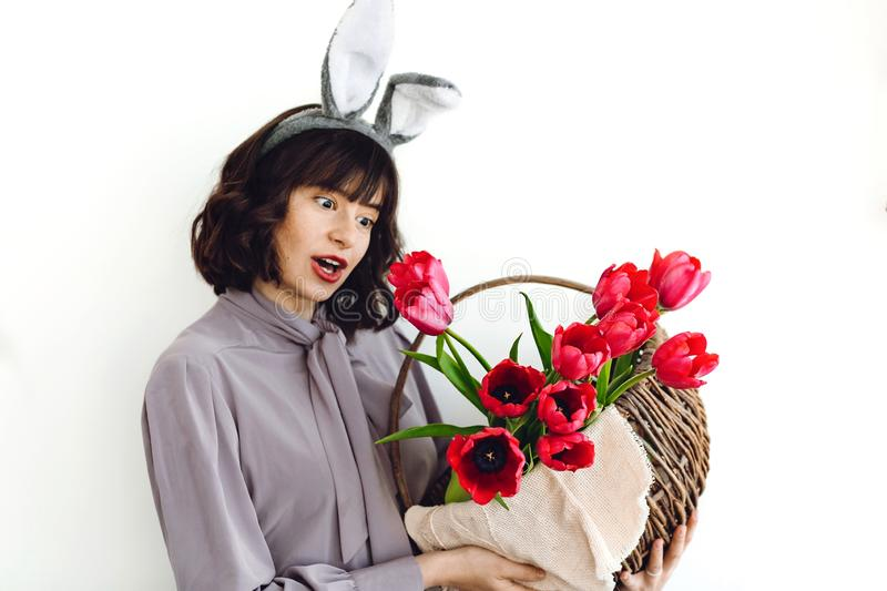 Beautiful girl in bunny ears with funny surprised emotions holding easter rustic basket with tulips on white background indoors,. Space for text. Spring stock image