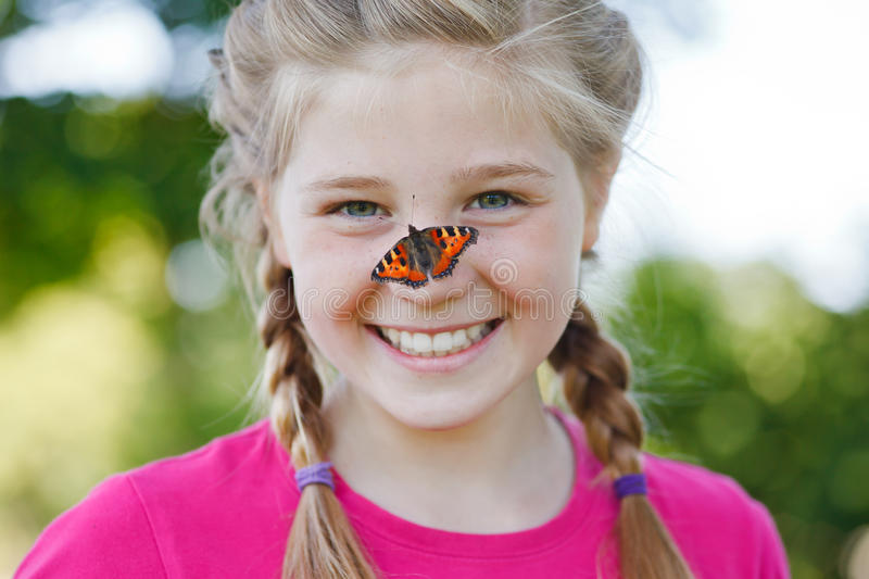 Beautiful girl with a butterfly on her nose. Butterfly sitting on a girls nose stock images