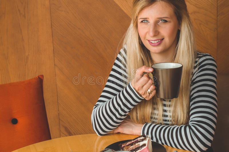Beautiful girl in a cafe enjoying a hot tea. Hipster girl holding hot tea. Refreshment drink in sunny day royalty free stock photography