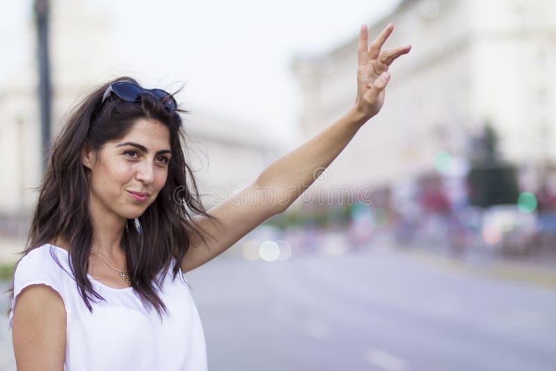 Beautiful girl calling taxi cab stock photo