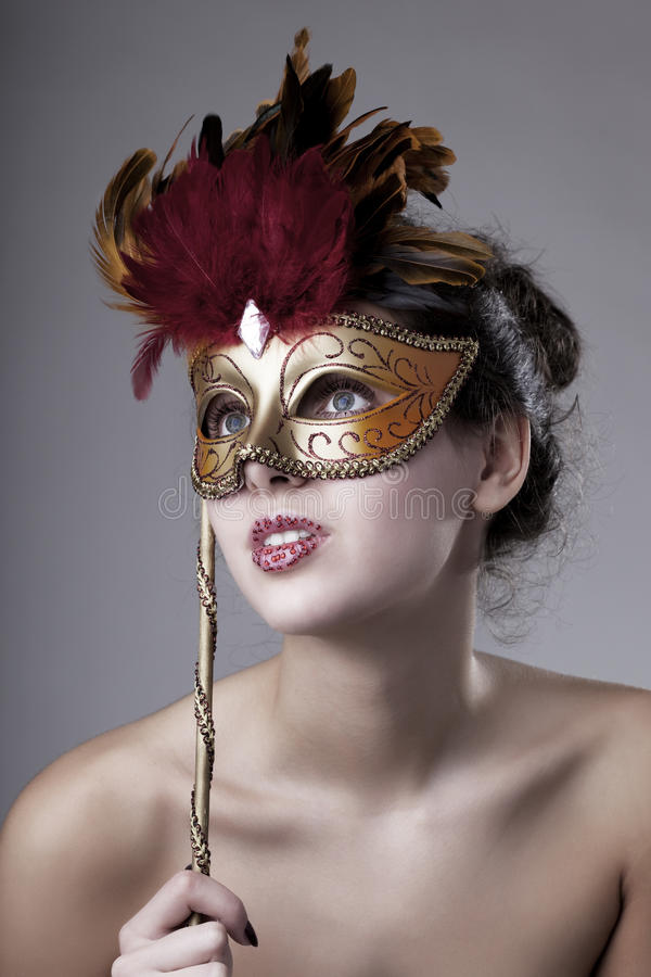 Beautiful girl with a carnival mask. The image of a beautiful girl with a carnival mask in the hands royalty free stock photography