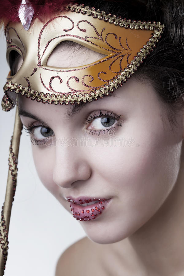 Beautiful girl with a carnival mask. The image of a beautiful girl with a carnival mask in the hands stock image