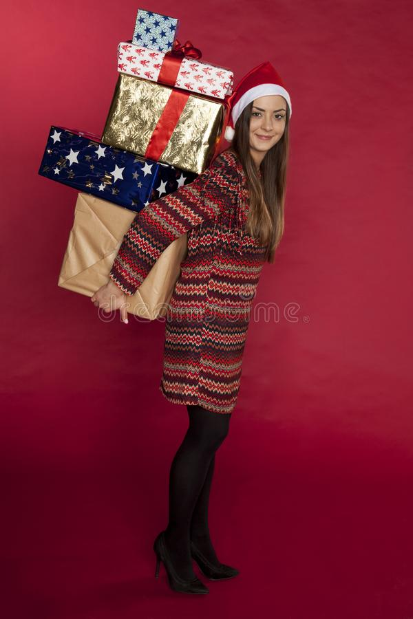 Beautiful girl carries a lot of gifts, happy face stock photography