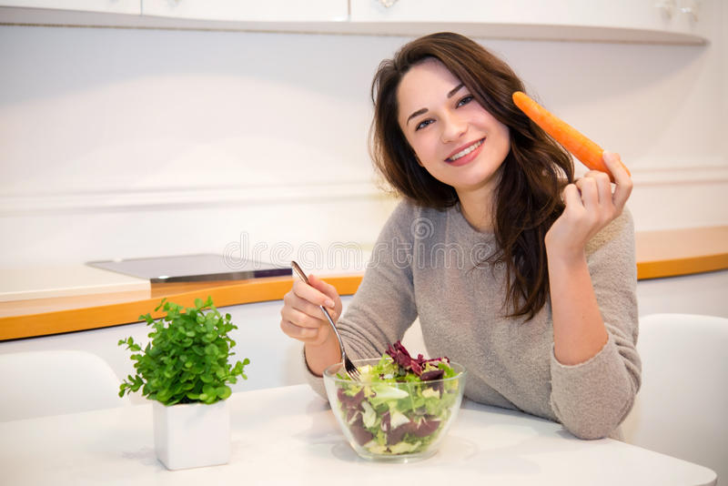 Beautiful girl with carrot and salad. In the kitchen stock photos