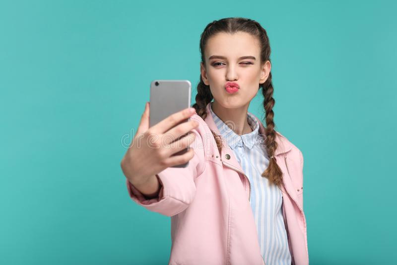 Beautiful girl in casual or hipster style, pigtail hairstyle, st. Anding, holding mobile smart phone and doing selfie or video calling with kiss, Indoor studio royalty free stock images