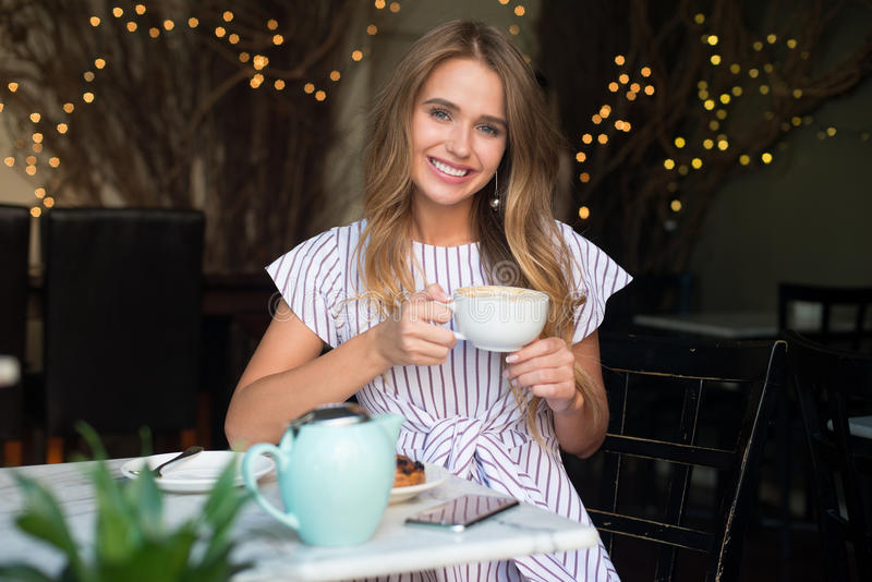 Beautiful girl with charming smile drinking cappuccino coffee in cafe. stock image