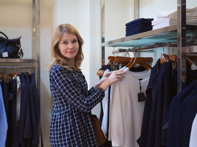 Beautiful girl chooses clothes in trendy boutique. Woman in a cl royalty free stock photos