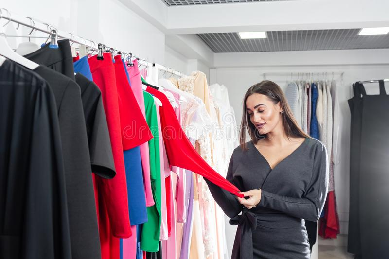 Beautiful girl are choosing clothes, while doing shopping in boutique. Sale, fashion, consumerism concept stock image