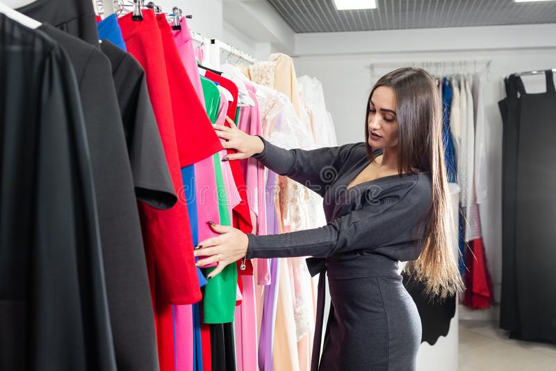 Beautiful girl are choosing clothes, while doing shopping in boutique. Sale, fashion, consumerism concept royalty free stock photos