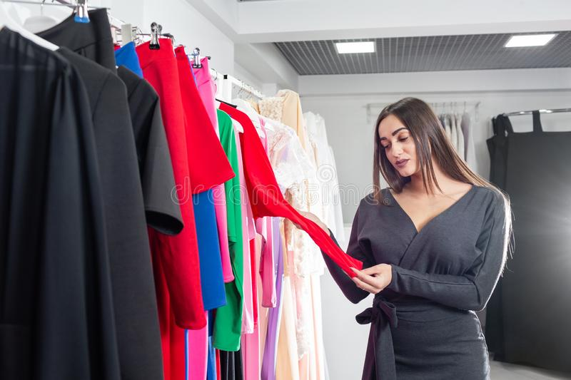 Beautiful girl are choosing clothes, while doing shopping in boutique. Sale, fashion, consumerism concept royalty free stock photography