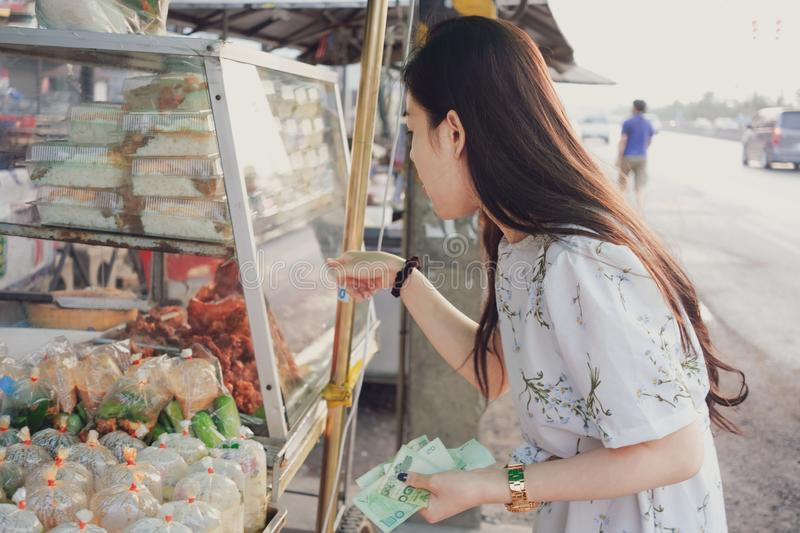 Beautiful girl choosing foods at the street market in Thailand stock photos