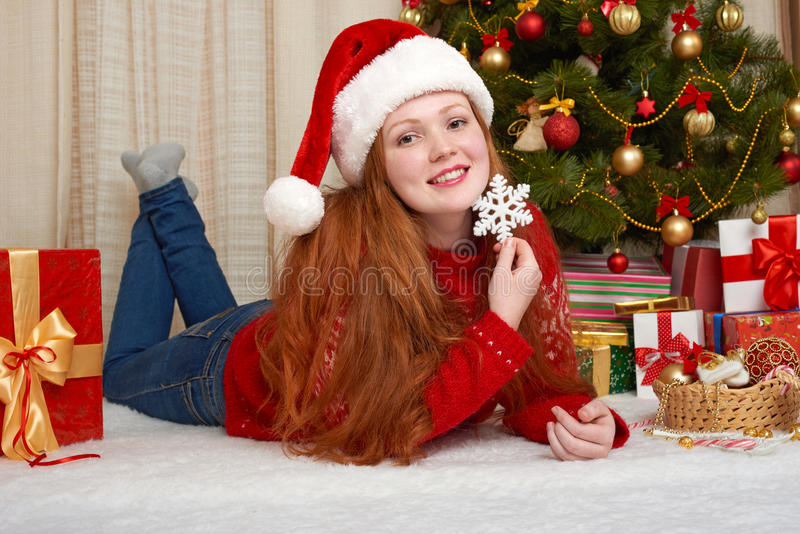 Beautiful girl in christmas decoration. Home interior with decorated fir tree and gifts. New year eve and winter holiday concept. stock images