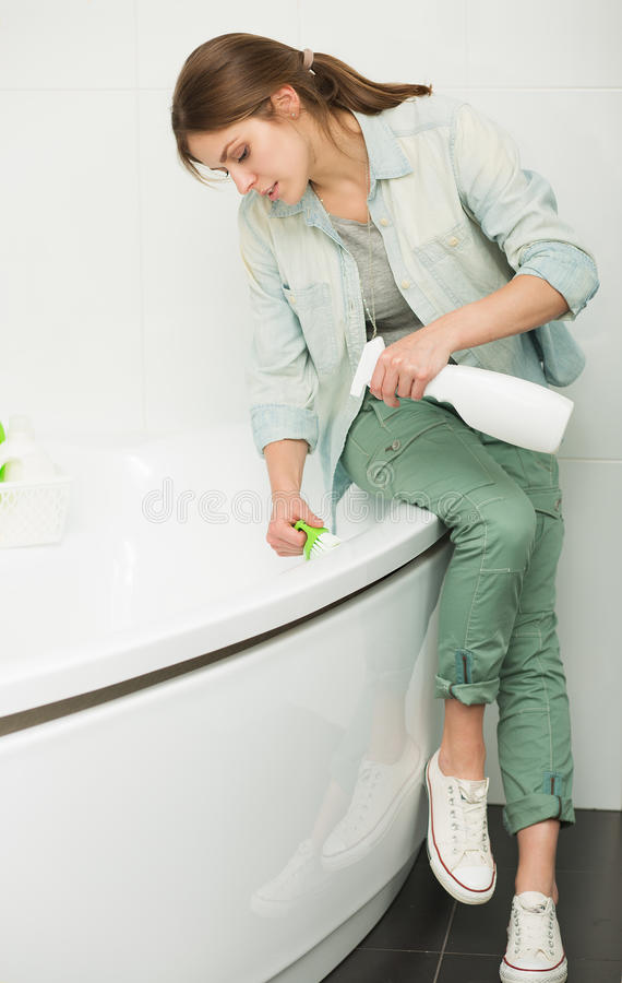 Beautiful girl cleaning up her house stock image