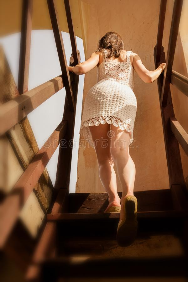 Beautiful girl climbs the stairs of a Cuban monument with a local craft dress stock photo