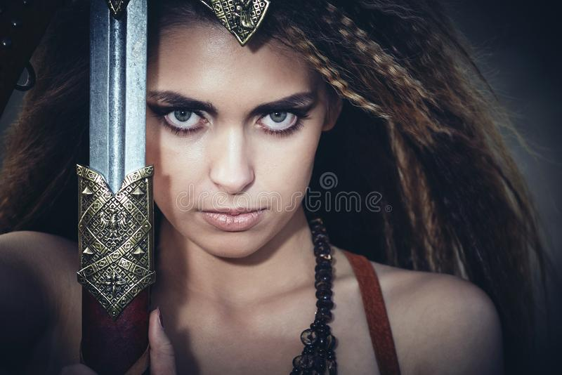 Beautiful girl in the clothes of a Viking or Amazon, with a sword on a background of stones. royalty free stock images