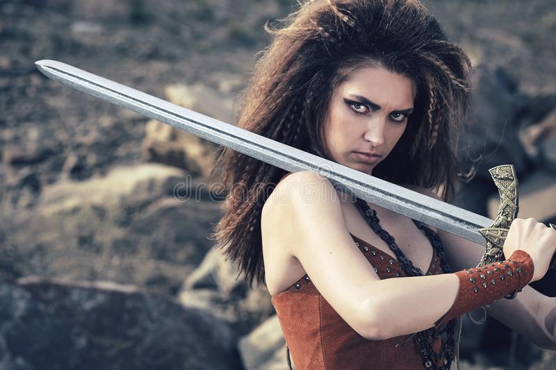 Beautiful girl in the clothes of a Viking or Amazon, with a sword on a background of stones. stock photo
