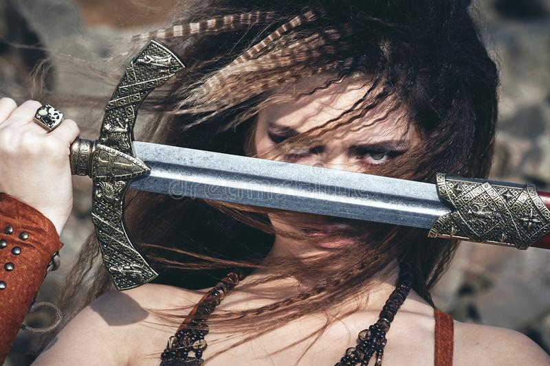 Beautiful girl in the clothes of a Viking or Amazon, with a sword on a background of stones. stock image