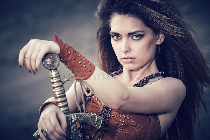 Beautiful girl in the clothes of a Viking or Amazon, with a sword on a background of stones. royalty free stock image
