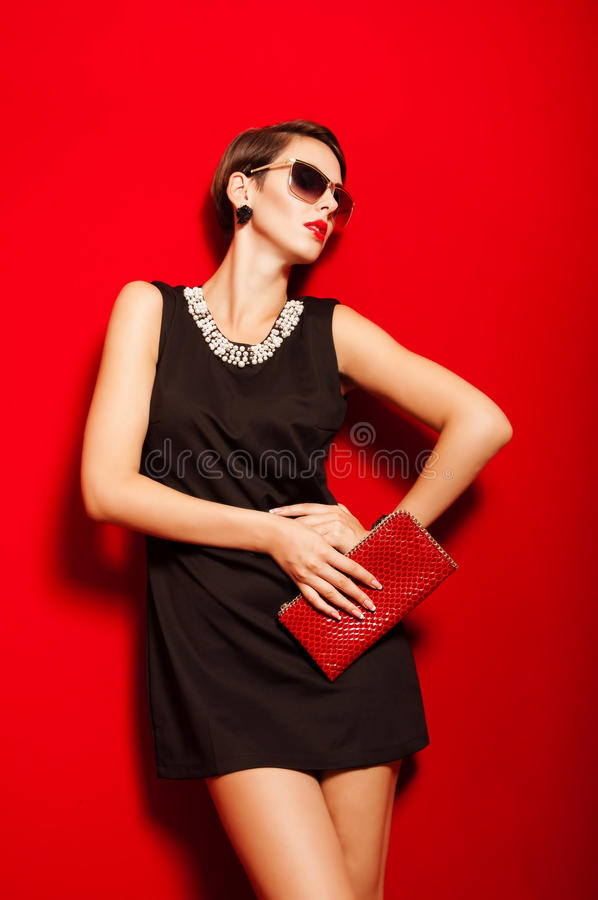 Beautiful girl with a clutch bag and sunglasses royalty free stock photography