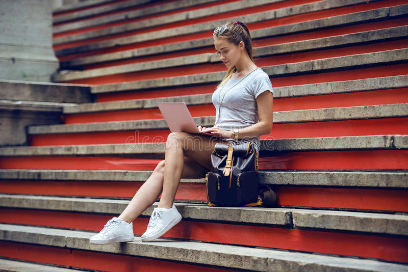 Beautiful girl college student working on laptop at campus. Woman sitting on the city steps and typing on laptop keyboard. royalty free stock images
