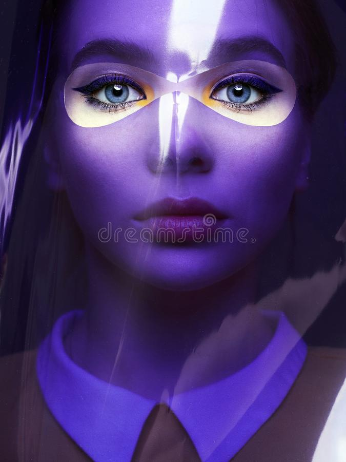 Beautiful girl with color make-up behind of colorful film. Female face art portrait stock image