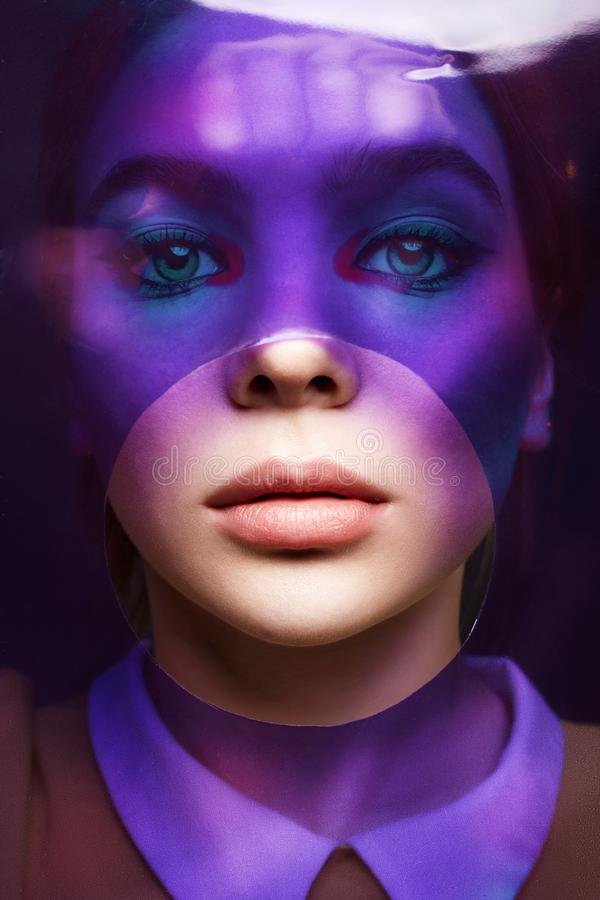Beautiful girl with color make-up behind of colorful film. Female face art portrait royalty free stock photography