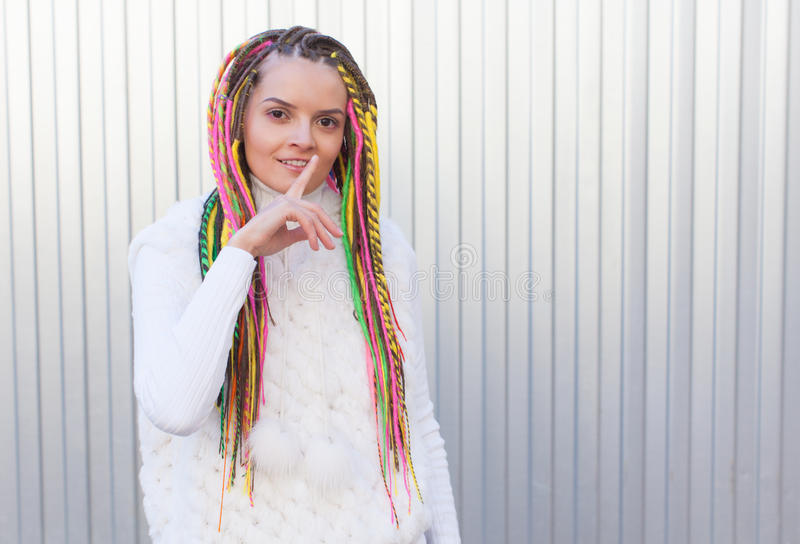 Beautiful girl with colored dreadlocks summer sunny day in a white jacket and lips finger asking for silence stock image