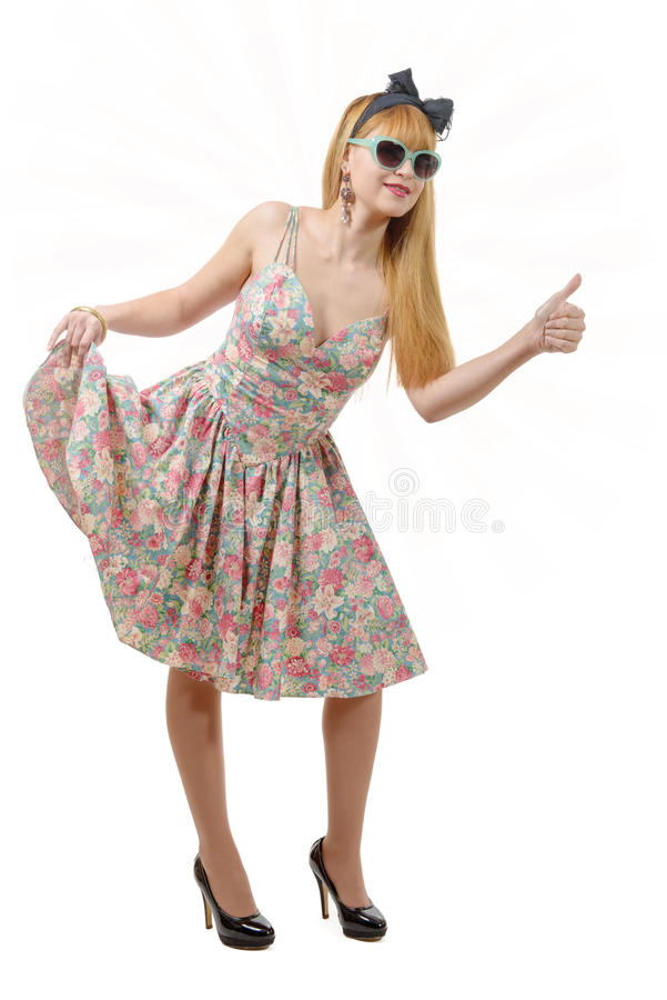 Beautiful girl with a colorful dress, hitchhiking. Beautiful pinup girl with a colorful dress, hitchhiking, on white royalty free stock images