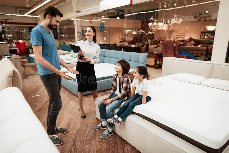 Beautiful girl consultant demonstrates orthopedic mattress to confident man with children in furniture store. Beautiful girl consultant demonstrates orthopedic royalty free stock image