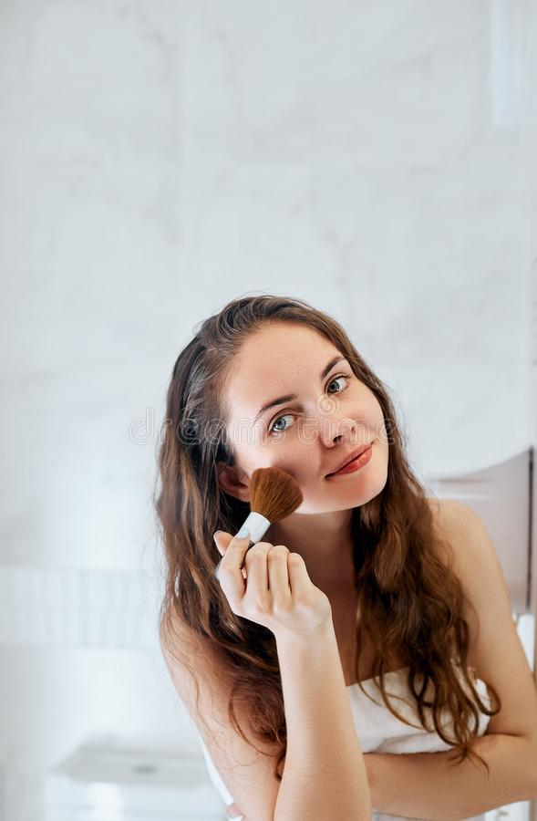 Beautiful girl with cosmetic powder brush for make up. Makeup. Make-up applying  for perfect skin royalty free stock image