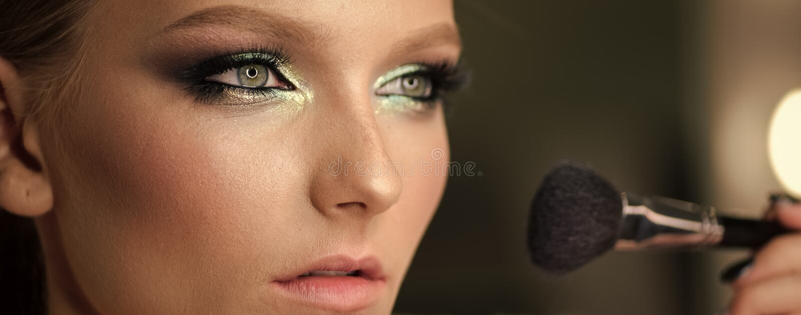 Beautiful girl with cosmetic powder brush for make up. Makeup. Make up applying for perfect skin. stock photos